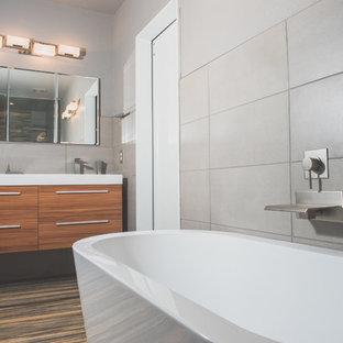 Diseño de cuarto de baño principal, contemporáneo, de tamaño medio, con armarios con paneles lisos, puertas de armario de madera oscura, jacuzzi, ducha abierta, sanitario de una pieza, baldosas y/o azulejos grises, paredes grises, lavabo suspendido, suelo gris, ducha abierta y encimeras blancas