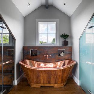 Idee per una grande stanza da bagno padronale industriale con pavimento in legno massello medio, ante lisce, ante beige, vasca freestanding, doccia a filo pavimento, pareti grigie, top piastrellato, pavimento marrone, porta doccia a battente e top bianco