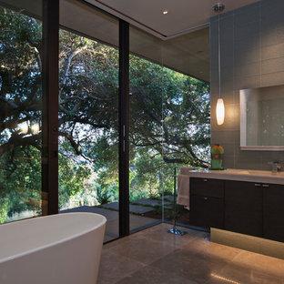 Immagine di un'ampia stanza da bagno moderna con ante lisce, ante in legno bruno, vasca freestanding, doccia alcova, WC sospeso, pistrelle in bianco e nero, piastrelle di vetro, pavimento in travertino, lavabo integrato e top in cemento