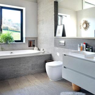 Imagen de cuarto de baño infantil, moderno, de tamaño medio, con armarios con paneles lisos, puertas de armario grises, bañera encastrada, sanitario de una pieza, baldosas y/o azulejos grises, paredes grises, lavabo encastrado, suelo gris y encimeras blancas