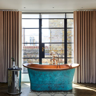 This is an example of a contemporary bathroom in London with a freestanding bath, dark hardwood flooring, brown floors and brick walls.