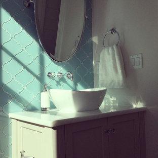 Esempio di una stanza da bagno costiera di medie dimensioni con ante grigie, piastrelle blu e piastrelle di vetro