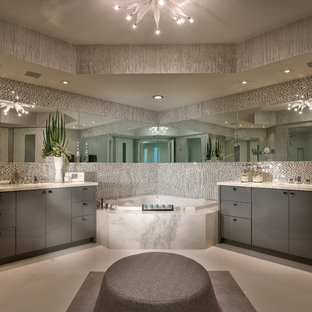 Foto di una stanza da bagno minimal con ante lisce, ante grigie, vasca ad angolo e piastrelle bianche