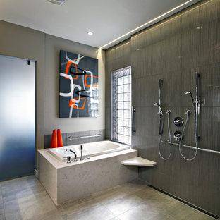 Diseño de cuarto de baño principal, actual, con ducha doble, armarios con paneles lisos, puertas de armario de madera en tonos medios, bañera encastrada, baldosas y/o azulejos grises y paredes grises