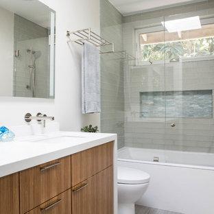 На фото: ванная комната в современном стиле с плоскими фасадами, фасадами цвета дерева среднего тона, ванной в нише, душем над ванной, стеклянной плиткой, полом из керамогранита, душевой кабиной, врезной раковиной, столешницей из искусственного кварца, серым полом, открытым душем и белой столешницей с