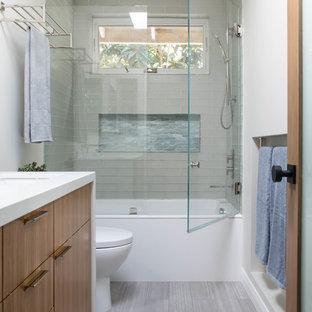Пример оригинального дизайна: ванная комната в современном стиле с плоскими фасадами, фасадами цвета дерева среднего тона, ванной в нише, душем над ванной, унитазом-моноблоком, стеклянной плиткой, полом из керамогранита, душевой кабиной, врезной раковиной, столешницей из искусственного кварца, серым полом, душем с распашными дверями и белой столешницей