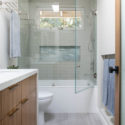 Trendy 3/4 glass tile porcelain tile and gray floor bathroom photo in Los Angeles with flat-panel cabinets, medium tone wood cabinets, a one-piece toilet, an undermount sink, quartz countertops, a hinged shower door and white countertops