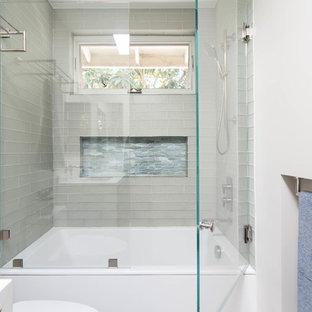 Idéer för att renovera ett funkis vit vitt badrum med dusch, med släta luckor, skåp i mellenmörkt trä, ett badkar i en alkov, en dusch/badkar-kombination, glaskakel, klinkergolv i porslin, ett undermonterad handfat, bänkskiva i kvarts, grått golv och dusch med gångjärnsdörr