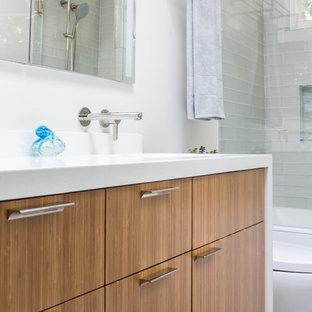 На фото: ванная комната в современном стиле с плоскими фасадами, фасадами цвета дерева среднего тона, ванной в нише, душем над ванной, стеклянной плиткой, полом из керамогранита, душевой кабиной, врезной раковиной, столешницей из искусственного кварца и белой столешницей с