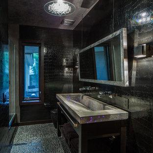Foto di una stanza da bagno minimal con lavabo rettangolare, top in cemento, piastrelle nere, nessun'anta, ante nere, WC monopezzo e pareti nere