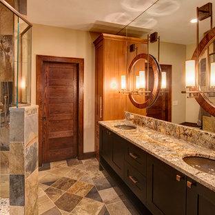 Modelo de cuarto de baño principal, rural, de tamaño medio, con lavabo bajoencimera, armarios con paneles lisos, puertas de armario de madera en tonos medios, encimera de granito, baldosas y/o azulejos verdes, baldosas y/o azulejos de piedra, paredes beige y suelo de pizarra