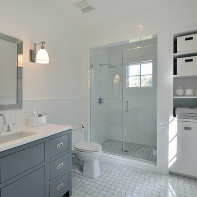 Transitional white tile alcove shower photo in New York with an undermount sink, flat-panel cabinets, blue cabinets, a one-piece toilet and white walls