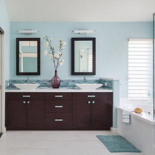 Неиссякаемый источник вдохновения для домашнего уюта: главная ванная комната среднего размера в современном стиле с плоскими фасадами, темными деревянными фасадами, синими стенами, настольной раковиной, душем с распашными дверями, полом из керамогранита, угловой ванной, угловым душем, синей плиткой, столешницей из искусственного кварца, стеклянной плиткой и белым полом