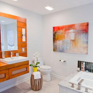 Foto di una stanza da bagno contemporanea con lavabo sospeso, ante arancioni, top in legno, vasca freestanding, doccia aperta e WC monopezzo