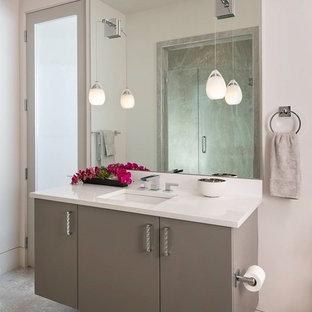Imagen de cuarto de baño con ducha, actual, de tamaño medio, con puertas de armario grises, baldosas y/o azulejos grises, lavabo bajoencimera, encimera de cuarzo compacto, armarios con paneles lisos, ducha empotrada, sanitario de una pieza, paredes blancas, suelo de travertino, suelo beige y ducha con puerta con bisagras