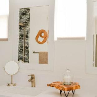 Immagine di una stanza da bagno per bambini classica di medie dimensioni con ante in stile shaker, ante bianche, vasca da incasso, vasca/doccia, WC monopezzo, piastrelle grigie, lastra di vetro, pareti bianche, pavimento in gres porcellanato, lavabo sottopiano, top in superficie solida, pavimento grigio, porta doccia scorrevole e top bianco