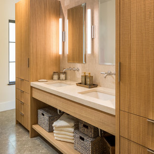 Design ideas for a contemporary bathroom in Charleston with flat-panel cabinets, light wood cabinets, beige tile, an undermount sink, grey floor and limestone.