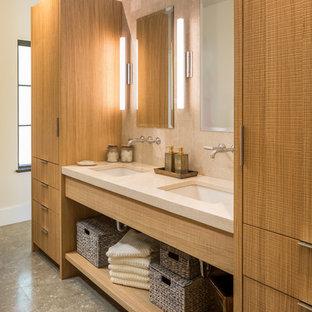 Стильный дизайн: ванная комната в современном стиле с плоскими фасадами, светлыми деревянными фасадами, бежевой плиткой, врезной раковиной, серым полом и плиткой из известняка - последний тренд