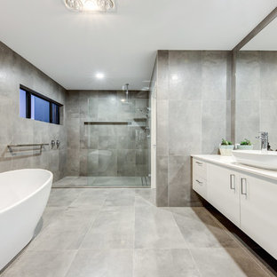 Inspiration for a contemporary master bathroom in Sunshine Coast with flat-panel cabinets, white cabinets, a freestanding tub, an alcove shower, gray tile, grey walls, a vessel sink, grey floor, an open shower, beige benchtops, porcelain tile, porcelain floors, a one-piece toilet and engineered quartz benchtops.