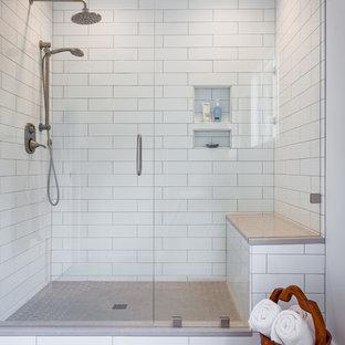 Ejemplo de cuarto de baño principal, tradicional renovado, de tamaño medio, con armarios estilo shaker, puertas de armario blancas, ducha empotrada, sanitario de dos piezas, baldosas y/o azulejos blancos, baldosas y/o azulejos de porcelana, paredes blancas, suelo de travertino, lavabo encastrado, encimera de acrílico, suelo beige y ducha con puerta con bisagras