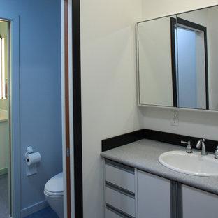 Imagen de cuarto de baño infantil, tradicional renovado, de tamaño medio, con lavabo encastrado, armarios con paneles lisos, puertas de armario blancas, encimera de acrílico, ducha esquinera, sanitario de dos piezas, paredes blancas y suelo de linóleo