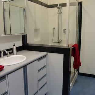 Diseño de cuarto de baño tradicional renovado, de tamaño medio, con lavabo encastrado, armarios con paneles lisos, puertas de armario blancas, encimera de acrílico, ducha esquinera, sanitario de dos piezas, paredes blancas y suelo de linóleo