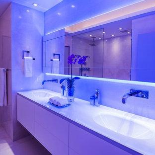 Пример оригинального дизайна: огромная главная ванная комната в стиле модернизм с плоскими фасадами, белыми фасадами, открытым душем, унитазом-моноблоком, белой плиткой, каменной плиткой, бежевыми стенами, полом из известняка, монолитной раковиной и стеклянной столешницей