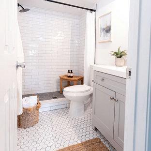 Lantlig inredning av ett litet vit vitt en-suite badrum, med grå skåp, en toalettstol med hel cisternkåpa, vit kakel, porslinskakel, grå väggar, klinkergolv i porslin, bänkskiva i kvartsit, vitt golv och dusch med duschdraperi