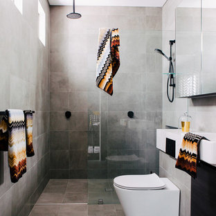 Photo of a contemporary shower room in Sydney with an alcove shower, a one-piece toilet, grey walls, grey tiles, cement tiles, a wall-mounted sink, grey floors and an open shower.