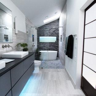 Foto de cuarto de baño principal, actual, de tamaño medio, con armarios con paneles lisos, puertas de armario grises, bañera exenta, ducha a ras de suelo, baldosas y/o azulejos grises, baldosas y/o azulejos de piedra, suelo de piedra caliza y paredes blancas