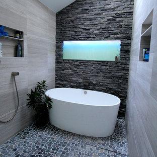 Modelo de cuarto de baño principal, contemporáneo, de tamaño medio, con bañera exenta, ducha a ras de suelo, baldosas y/o azulejos grises, baldosas y/o azulejos de piedra y suelo de piedra caliza