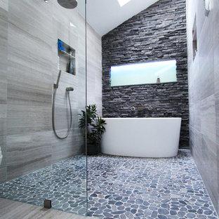Идея дизайна: главная ванная комната среднего размера в современном стиле с отдельно стоящей ванной, душем без бортиков, серой плиткой, каменной плиткой и полом из известняка