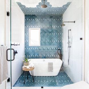 Immagine di una stanza da bagno minimal con vasca freestanding, zona vasca/doccia separata, piastrelle blu, piastrelle bianche, pareti bianche, pavimento blu e porta doccia a battente