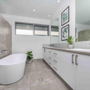 Large contemporary bathroom in Perth with flat-panel cabinets, white cabinets, a freestanding tub, porcelain tile, white walls, a drop-in sink, white benchtops, gray tile and grey floor.
