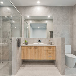 Photo of a contemporary 3/4 bathroom in Sunshine Coast with flat-panel cabinets, light wood cabinets, an alcove shower, a two-piece toilet, gray tile, a drop-in sink, grey floor and white benchtops.
