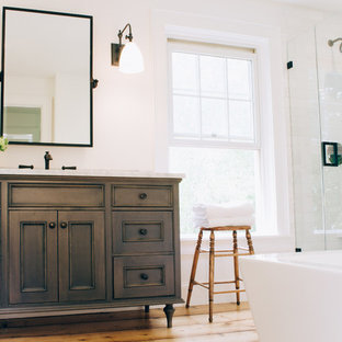 Inspiration for a mid-sized cottage master white tile and stone tile light wood floor bathroom remodel in New York with gray cabinets, a one-piece toilet, white walls, an undermount sink, marble countertops and recessed-panel cabinets