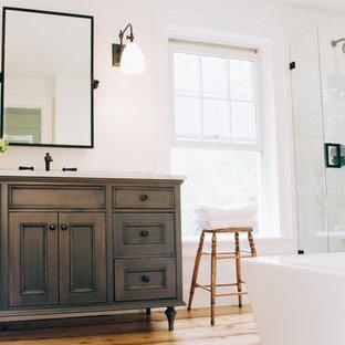 Esempio di una stanza da bagno padronale country di medie dimensioni con ante grigie, vasca freestanding, doccia ad angolo, WC monopezzo, piastrelle bianche, piastrelle in pietra, pareti bianche, parquet chiaro, lavabo sottopiano, top in marmo e ante con riquadro incassato
