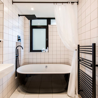 Design ideas for a small contemporary family bathroom in London with open cabinets, a freestanding bath, a shower/bath combination, white tiles, porcelain tiles, porcelain flooring, a wall-mounted sink, white floors, a shower curtain and white walls.