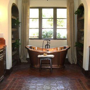 Idéer för ett mycket stort medelhavsstil badrum, med luckor med upphöjd panel, skåp i mörkt trä, ett fristående badkar, en toalettstol med hel cisternkåpa, beige kakel, brun kakel, flerfärgad kakel, röd kakel, porslinskakel, beige väggar, klinkergolv i porslin, ett nedsänkt handfat, granitbänkskiva och rött golv