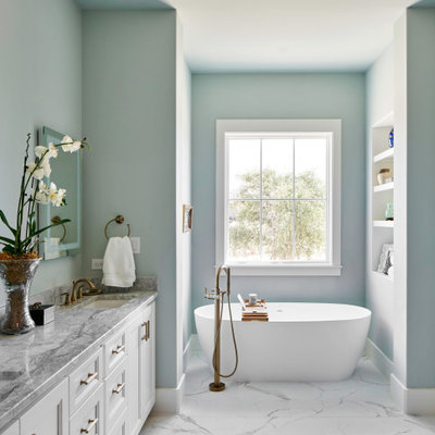 Freestanding bathtub - country white floor freestanding bathtub idea in Other with recessed-panel cabinets, white cabinets, blue walls, an undermount sink and gray countertops