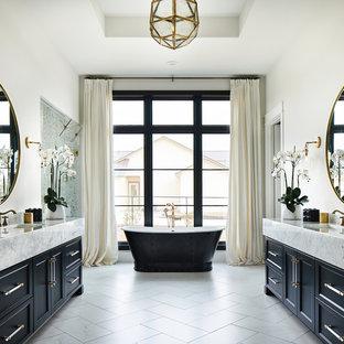 Immagine di una stanza da bagno padronale chic con ante con riquadro incassato, ante blu, vasca freestanding, pareti bianche, lavabo integrato, pavimento bianco e top bianco