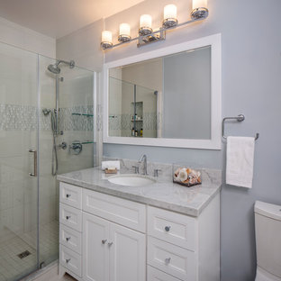 Inspiration for a small transitional master white tile and porcelain tile porcelain floor and white floor alcove shower remodel in Miami with shaker cabinets, white cabinets, a two-piece toilet, gray walls, an undermount sink, marble countertops and a hinged shower door