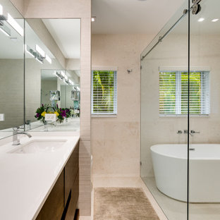 This is an example of a large contemporary master bathroom in Miami with flat-panel cabinets, medium wood cabinets, a freestanding tub, a shower/bathtub combo, a two-piece toilet, beige tile, stone tile, beige walls, porcelain floors, a wall-mount sink, tile benchtops, beige floor, a hinged shower door, white benchtops, a niche, a double vanity, a built-in vanity and panelled walls.
