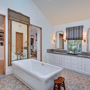 Elegant master cement tile floor and gray floor freestanding bathtub photo in Los Angeles with shaker cabinets, white cabinets, white walls, an undermount sink and gray countertops