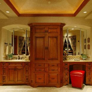 Imagen de cuarto de baño principal, rural, grande, con armarios con paneles con relieve, puertas de armario de madera oscura, paredes beige, suelo de piedra caliza, lavabo bajoencimera y suelo beige
