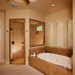 Example of a large minimalist master beige tile corner shower design in Austin with a vessel sink, dark wood cabinets, granite countertops and beige walls