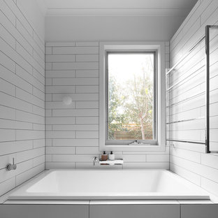 Contemporary bathroom in Melbourne with a drop-in tub, white tile and white walls.
