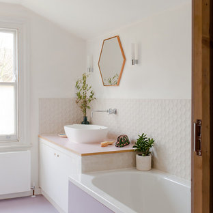 Photo of a contemporary bathroom in London with flat-panel cabinets, white cabinets, an alcove bath, white tiles, white walls, a vessel sink, purple floors and white worktops.