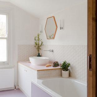 Modern inredning av ett vit vitt badrum, med släta luckor, vita skåp, ett badkar i en alkov, vit kakel, vita väggar, ett fristående handfat och lila golv