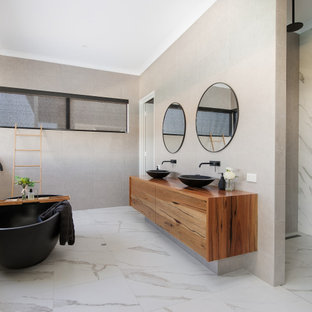 Inspiration for a large contemporary master bathroom in Perth with flat-panel cabinets, medium wood cabinets, a freestanding tub, gray tile, porcelain tile, a vessel sink, wood benchtops, grey floor, brown benchtops, a double vanity and a floating vanity.